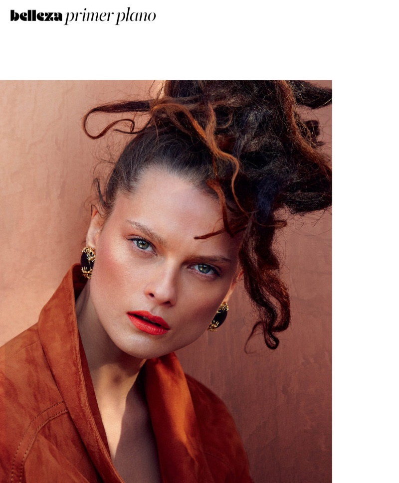 Wearing a curly updo, Elena Melnik models Balmain jacket and Alolo earrings
