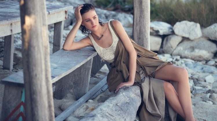 Posing on the beach, Eliza Cummings wears neutral hues