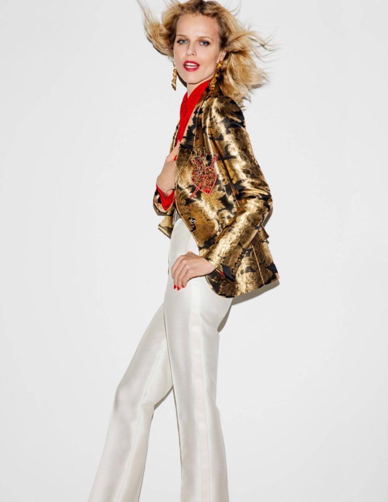 Eva Herzigova poses in Schiaparelli gold brocade jacket, red shirt and white pants