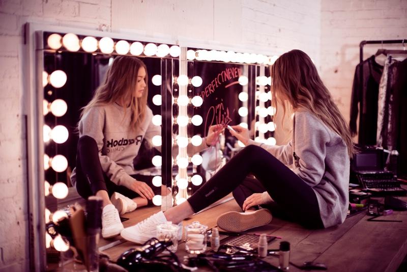 Writing in a mirror, Gigi Hadid writes Reebok's #PerfectNever slogan