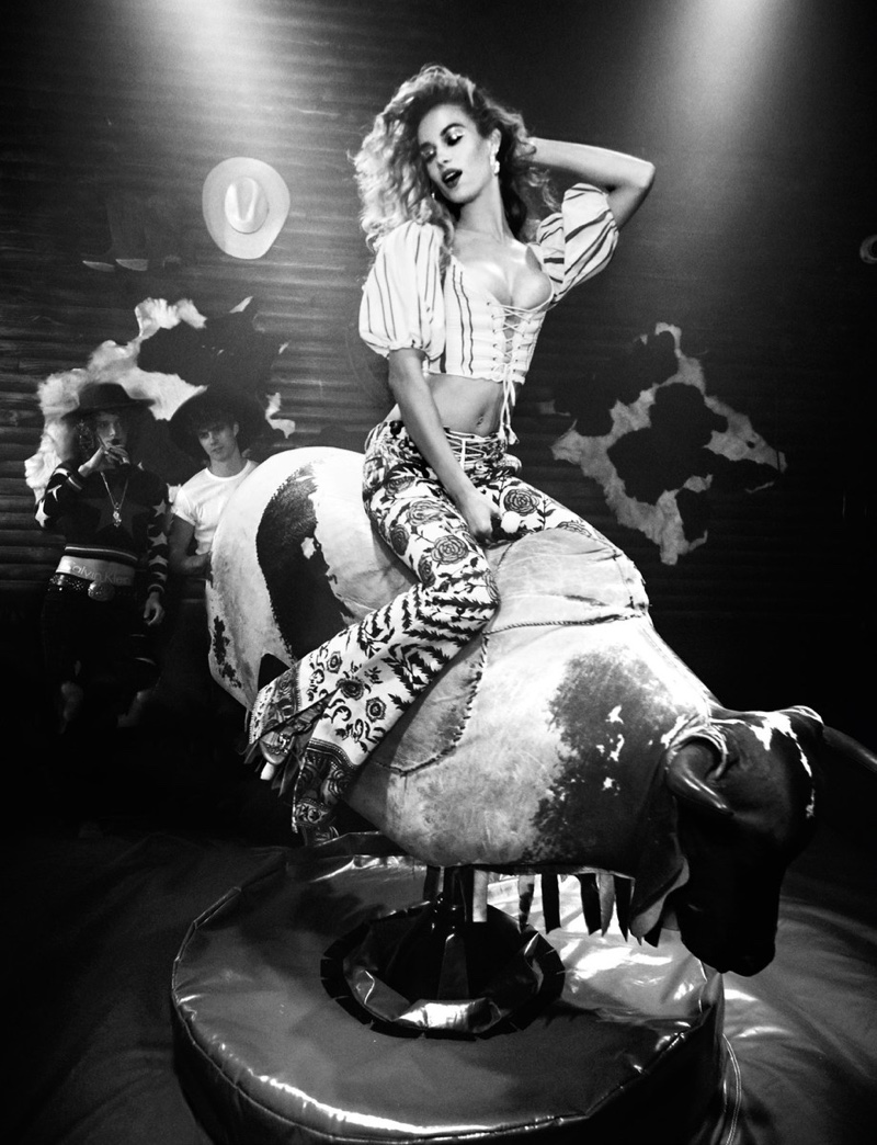 Riding a mechanical bull, Hannah Ferguson wears corset top with flared trousers
