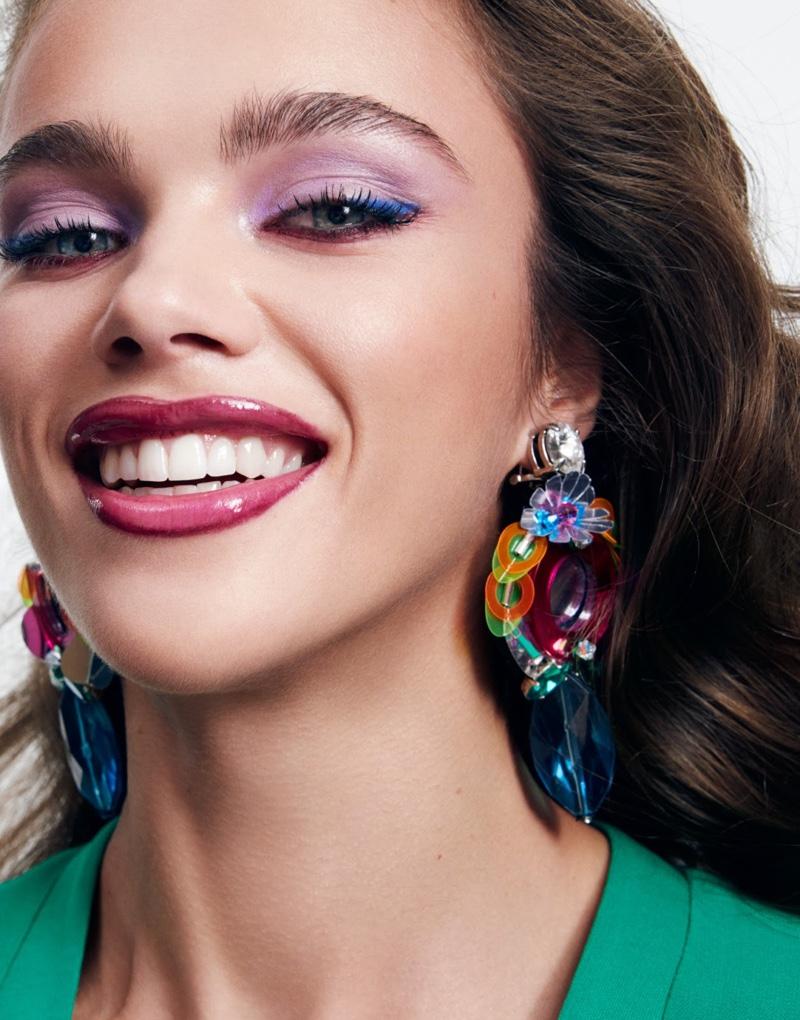 Flashing a smile, Jena Goldsack models Balmain dress and Miu Miu earrings
