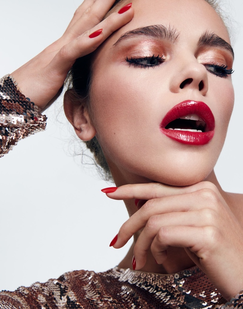 Jena Goldsack models bold red lipstick with matching manicure, dress by Tom Ford
