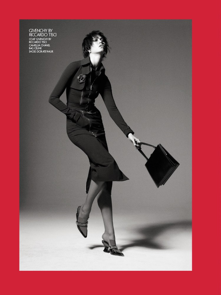 Photographed in black and white, Karlie Kloss models Givenchy coat, Chanel Camellia broach, Celine bag and Dorateymur shoes