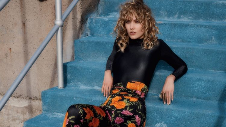 Model Karlie Kloss wears Balenciaga top, floral print pants and boots