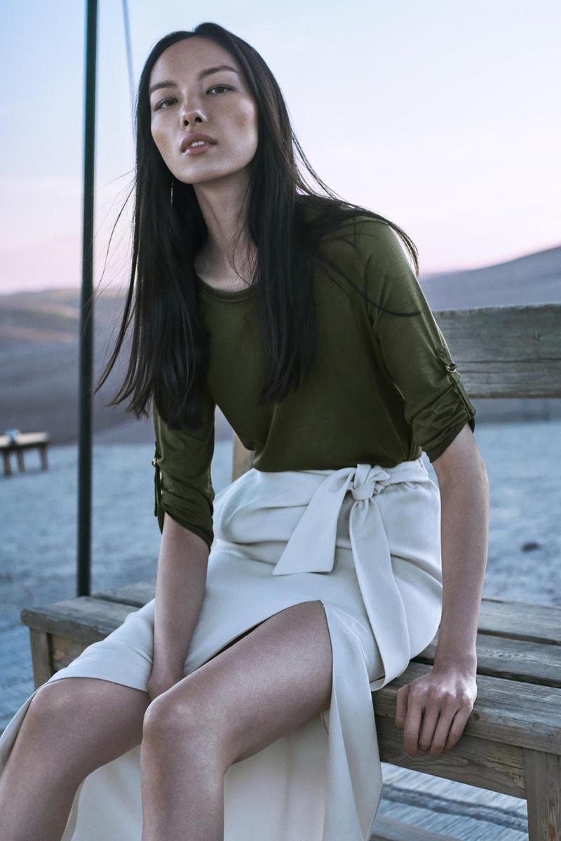 Fei Fei Sun wears khaki green shirt and maxi skirt with slit from Massimo Dutti