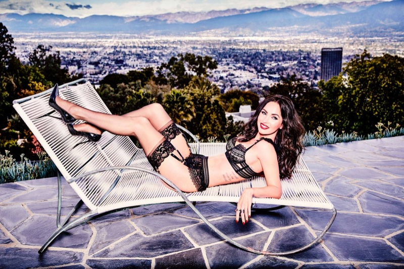Lounging poolside, Megan Fox models black lingerie by Frederick's of Hollywood