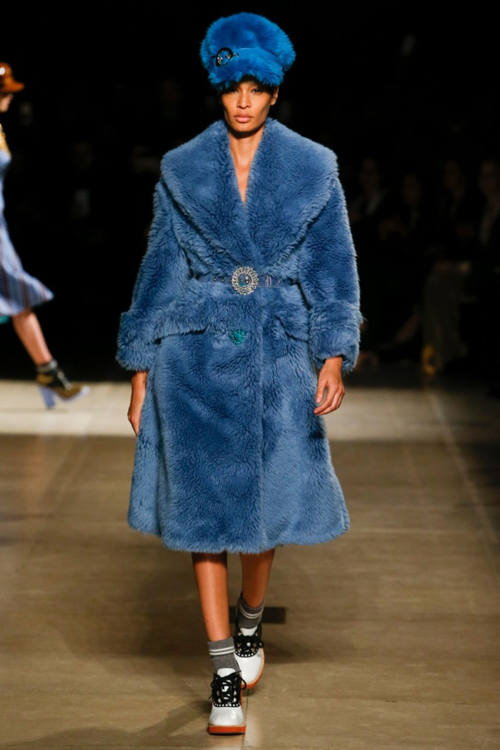 Joan Smalls wears blue fur hat and coat with crystal embellished belt from Miu Miu's fall-winter 2017 collection