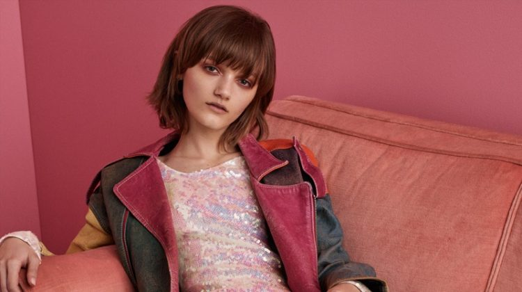Lounging on a couch, Peyton Knight models vintage leather jacket and Christopher Kane sequined dress
