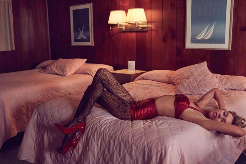 Posing in bed, Stella Maxwell wears red bustier and briefs