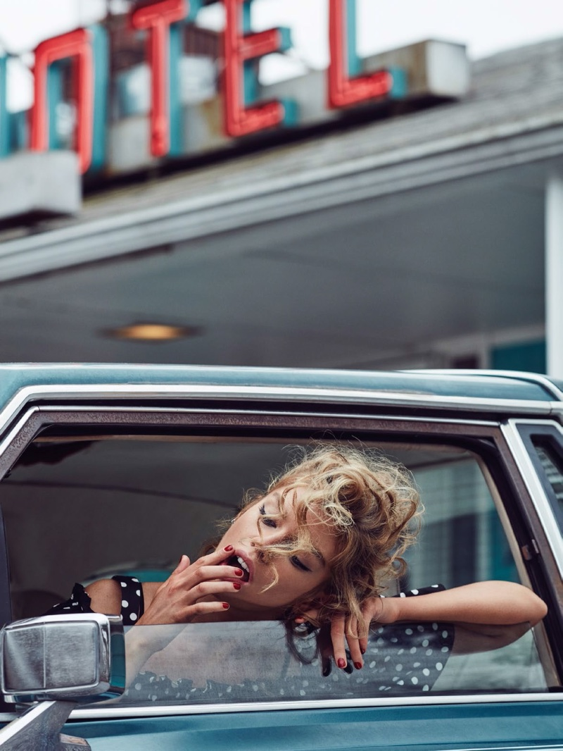 Stella Maxwell poses in a car wearing a polka dot print off-the-shoulder dress