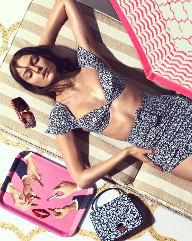 Soaking up the sun, model wears Michael Kors Collection bikini top, bottoms and leather satchel