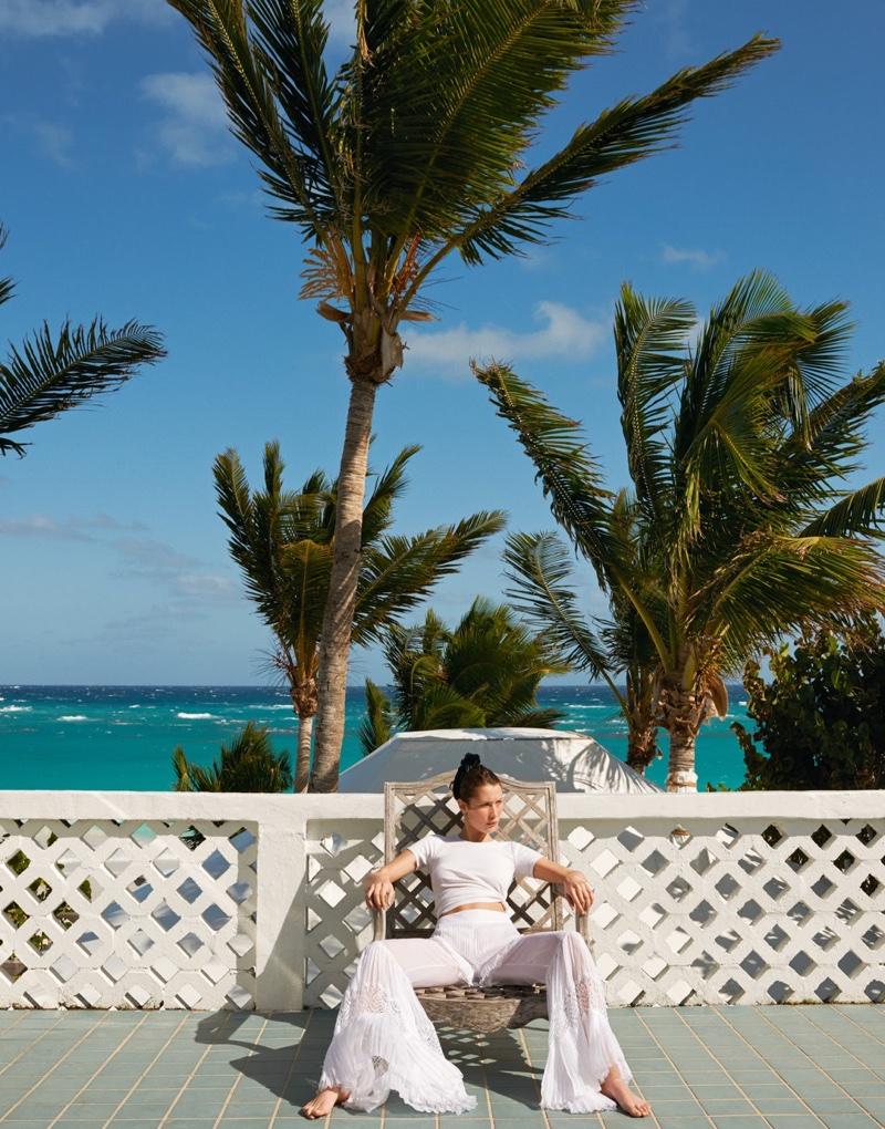 Posing in the Bahamas, Bella Hadid models white t-shirt and flared pants
