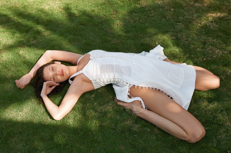Posing in the grass, Bella Hadid models white Chloe dress