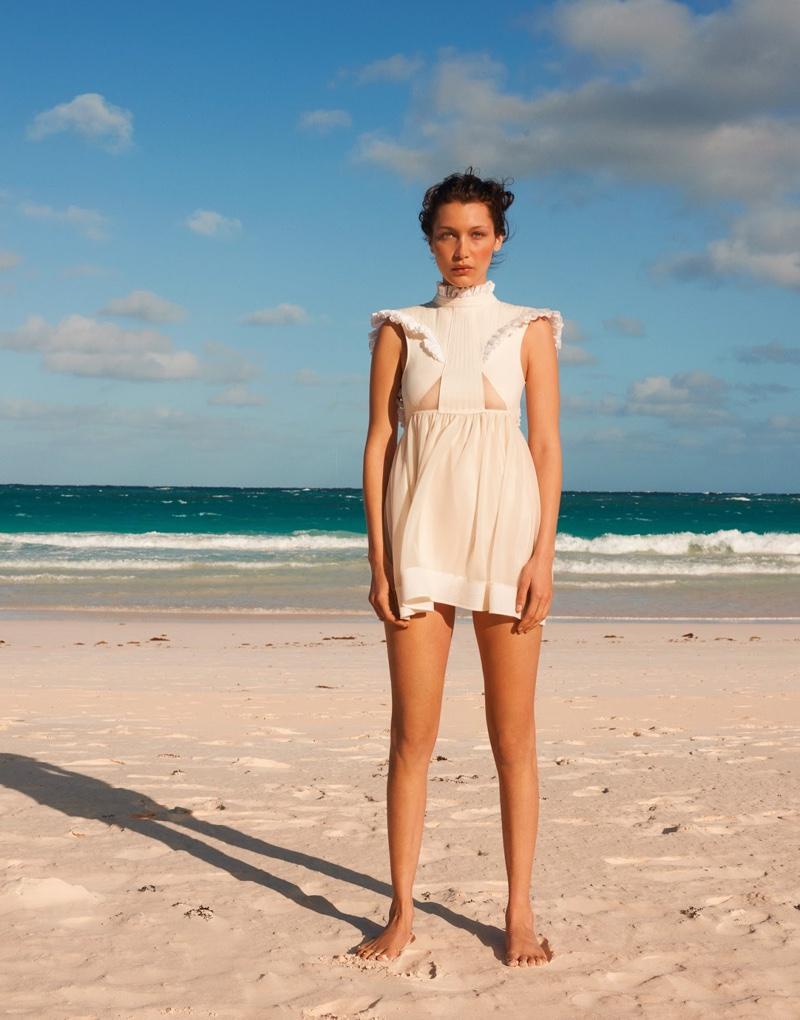 On the beach, Bella Hadid models a little white dress