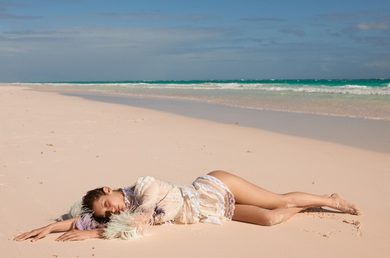 Washed ashore, Bella Hadid poses in the sand wearing sheer dress with feathers