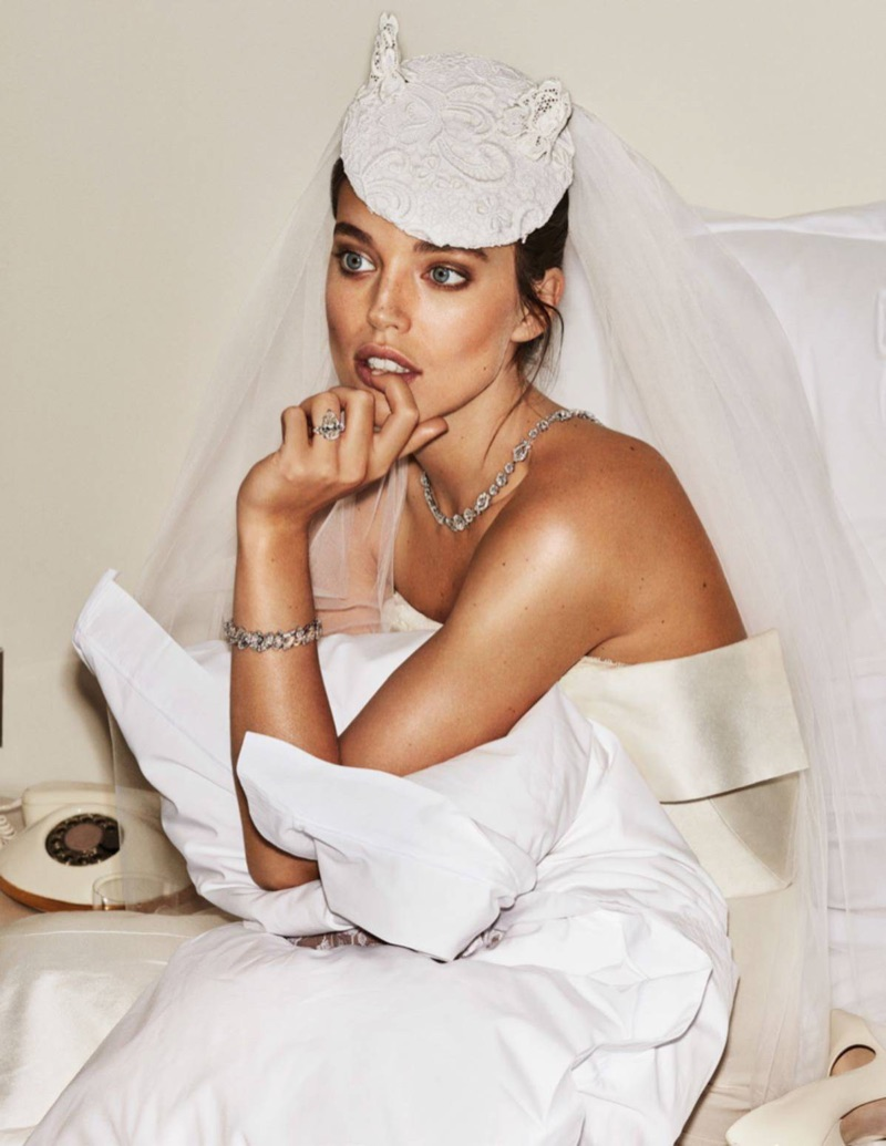 Sitting on a bed, Emily DiDonato models Graff jewelry with Oscar de la Renta Bridal wedding dress