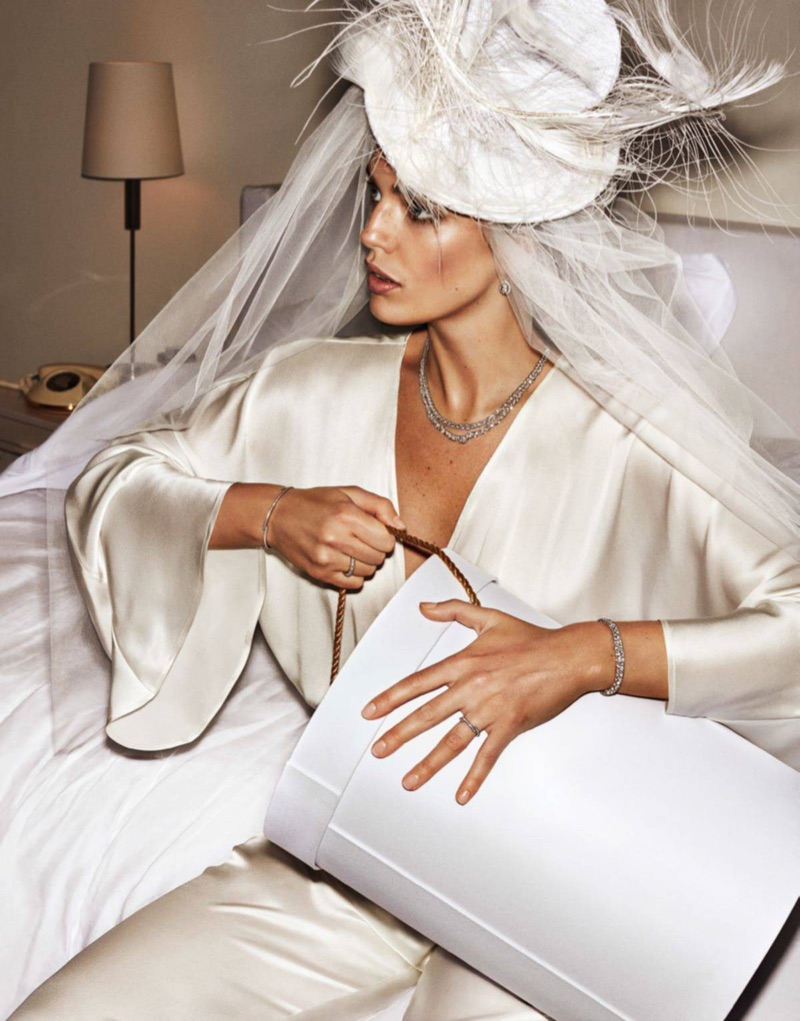 Looking bridal chic in white, Emily DiDonato poses in Anya Caliendo feather hat and Mae's Sunday jumpsuit