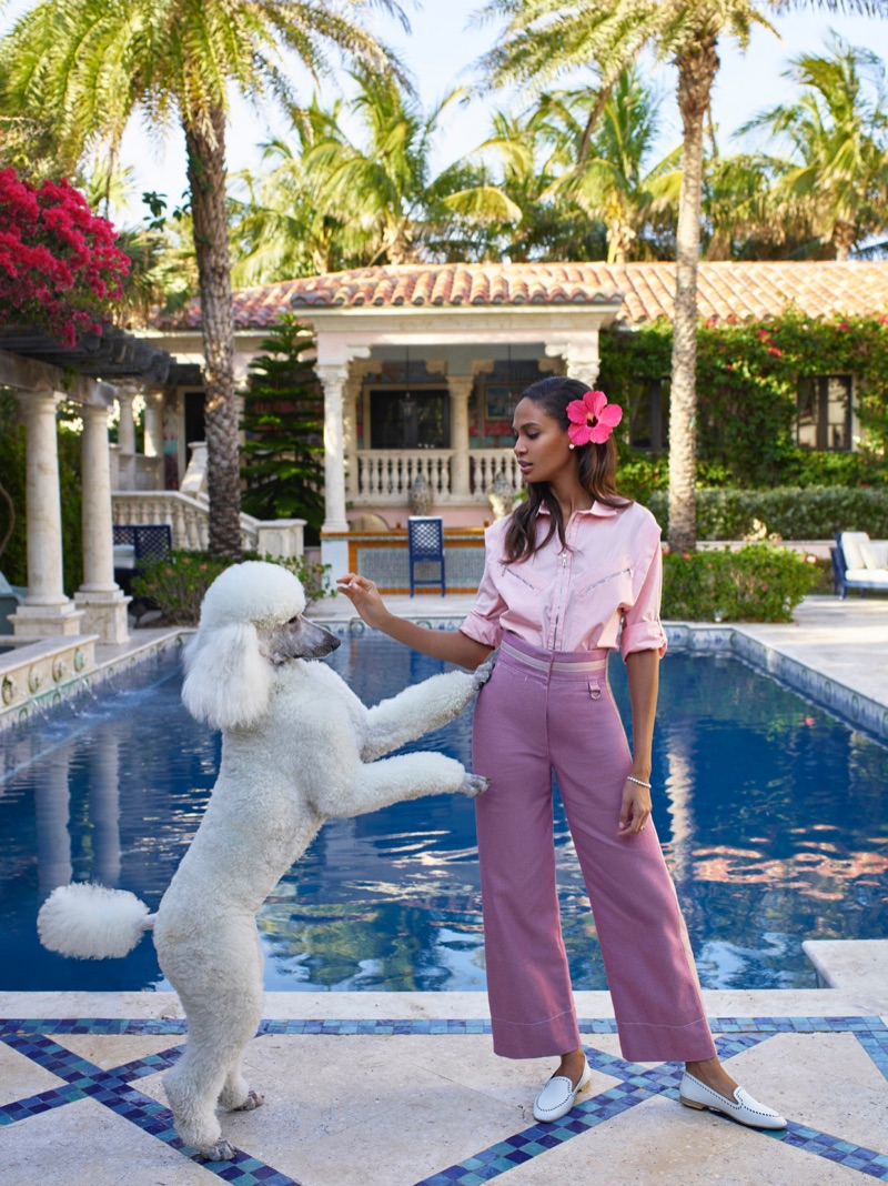 Posing with a poodle, Joan Smalls wears pink top, mauve pants and white loafers