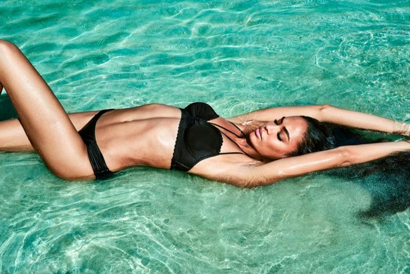 Posing in the ocean, Joan Smalls models black swimsuit set from Smart & Sexy Swim Secret
