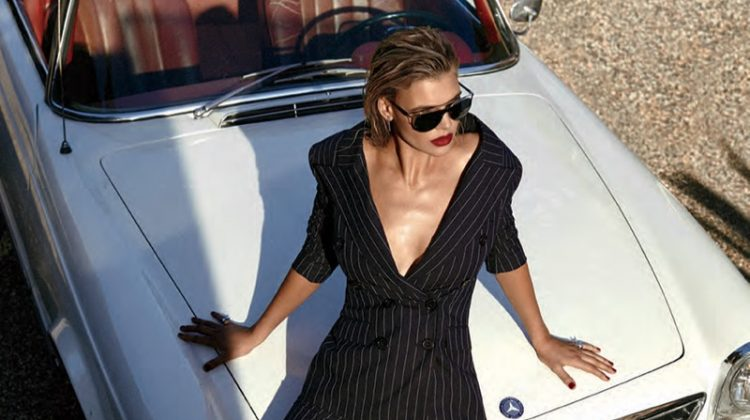 Posing on a convertible, Kelly Rohrbach models pinstriped pantsuit from Monse with Michael Kors sunglasses and Jimmy Choo heels