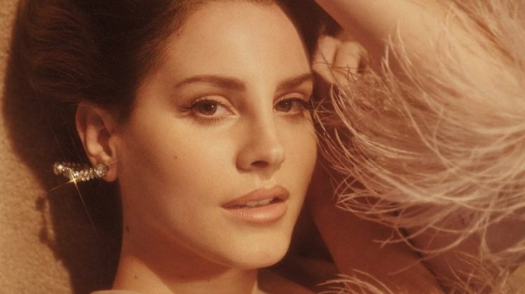 Looking ultra-glam, Lana Del Rey poses in Prada chiffon and ostrich feather dress with Gillian Horsup earrings