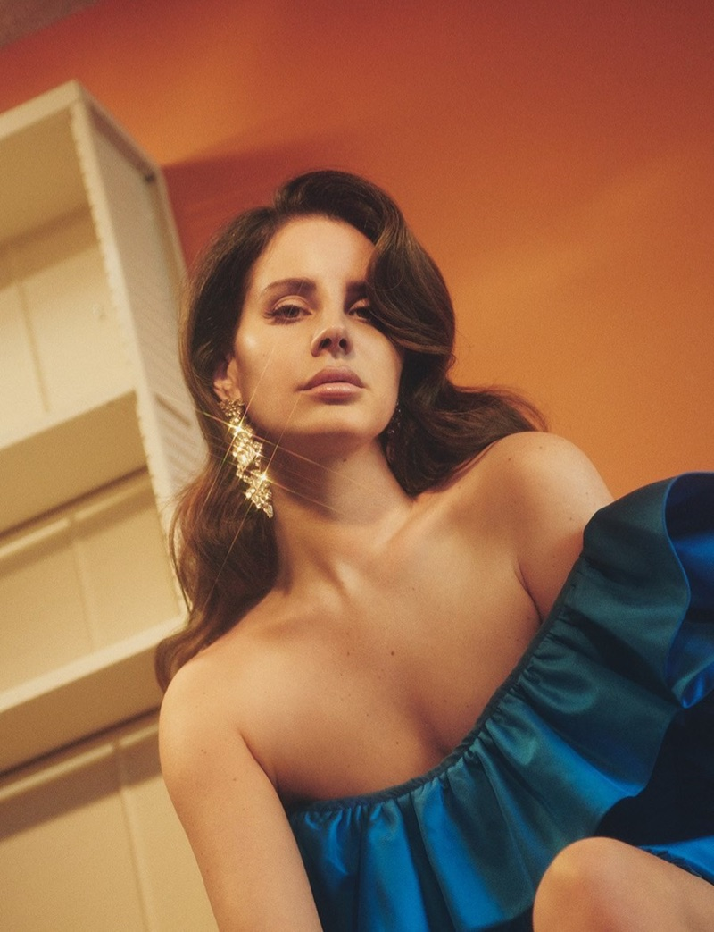 Flaunting some shoulder, Lana Del Rey models Gucci silk asymmetrical dress with Saint Laurent crystal earrings