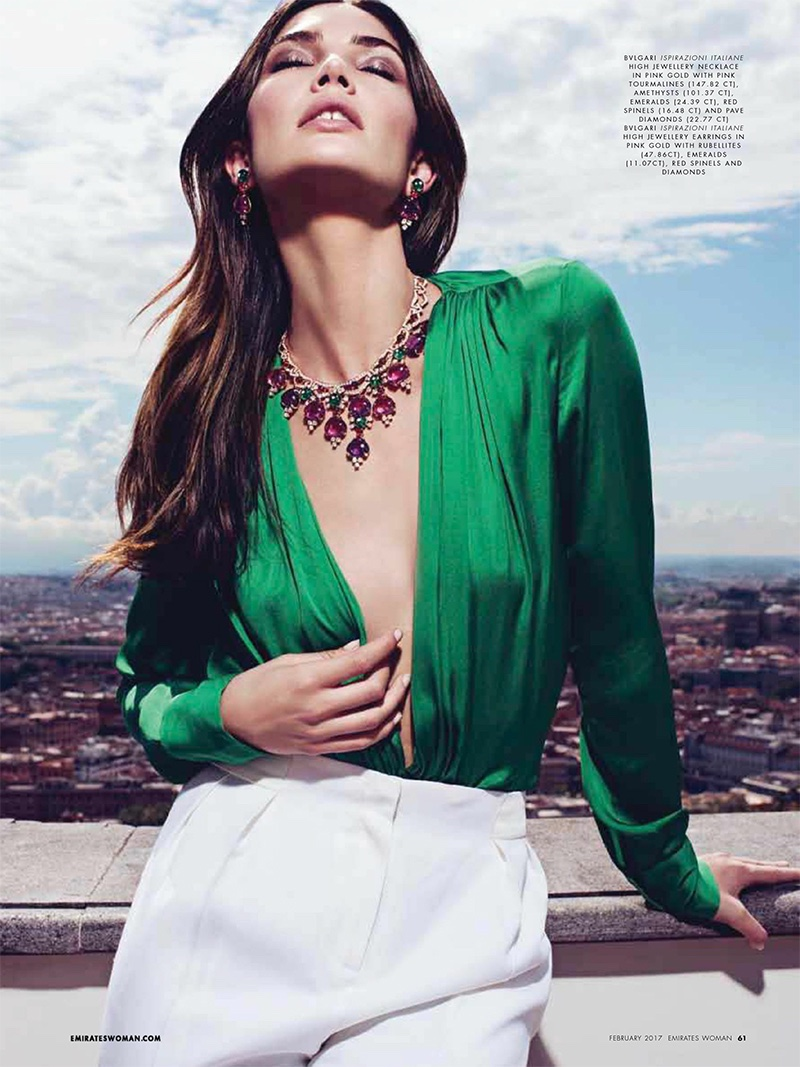 Lily Aldridge models green dress with plunging neckline and white trousers. Jewelry from Bulgari.