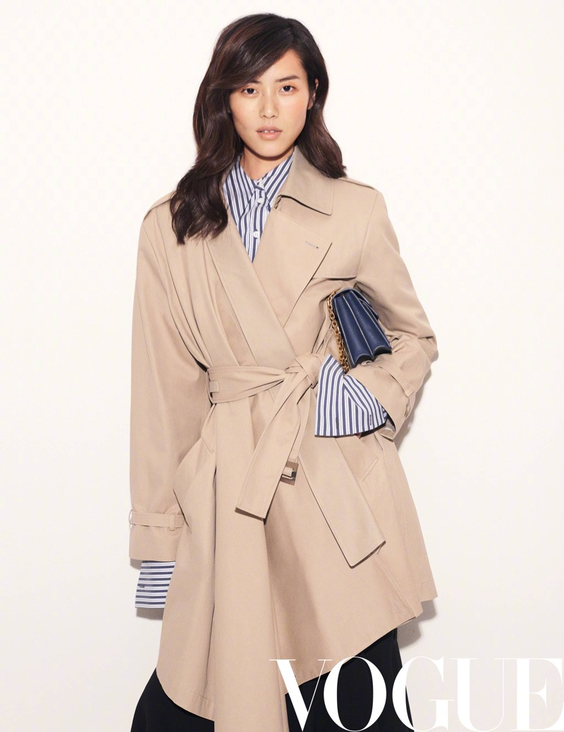 Liu Wen covers up in a brown trench coat and striped shirt