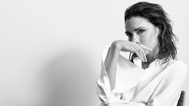 Victoria Beckham poses in button-up blouse, adidas track pants and sneakers