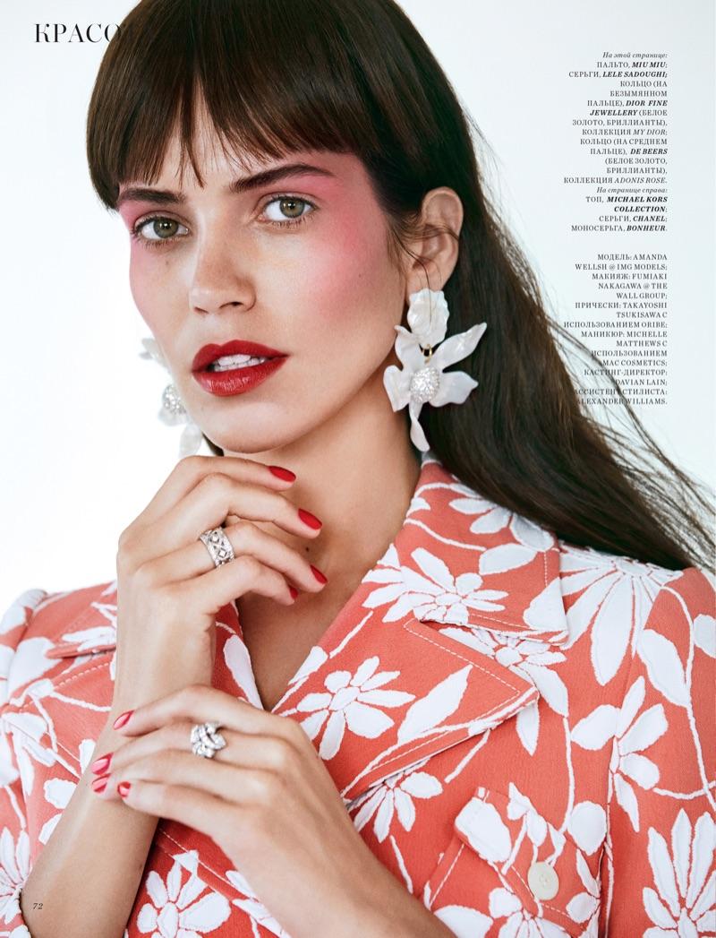 Wearing a Miu Miu coat, Amanda Wellsh shows off a vibrant red shade of lipstick
