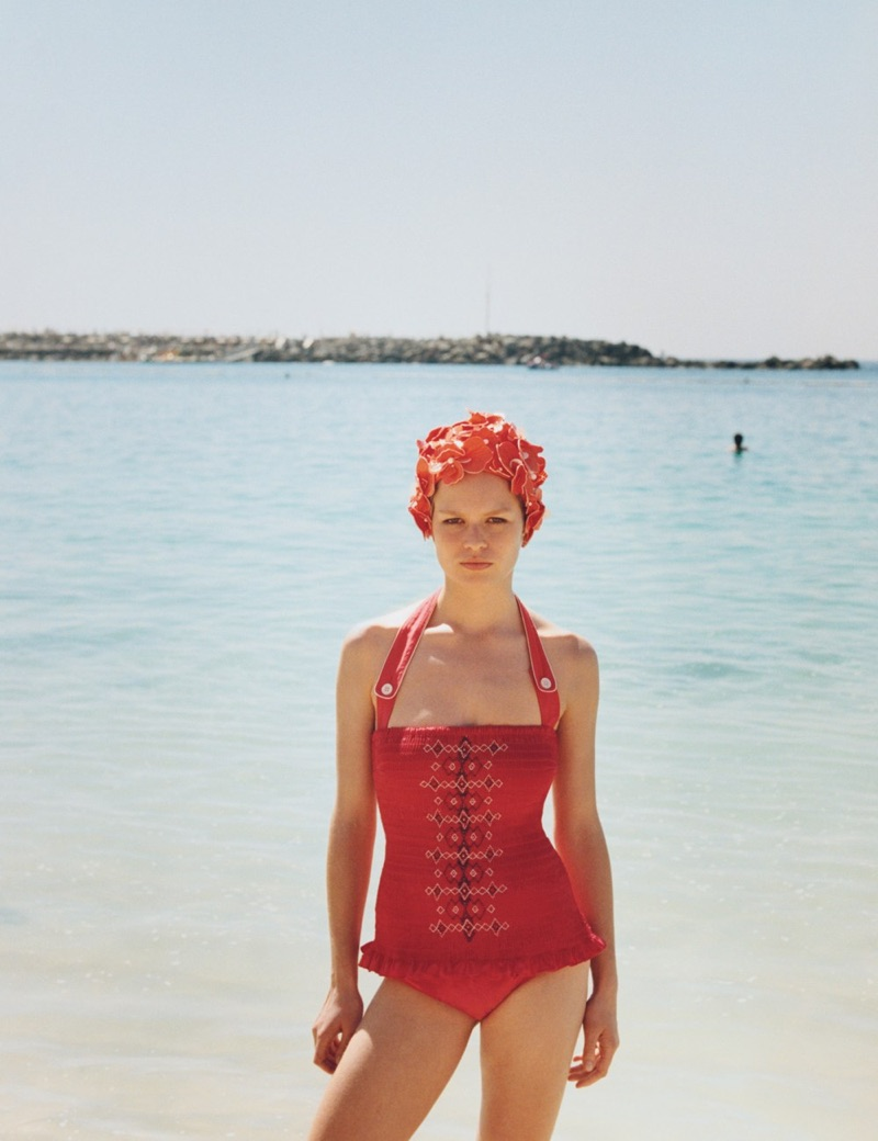 Anna Ewers stands out in red wearing Miu Miu swimsuit and swim cap
