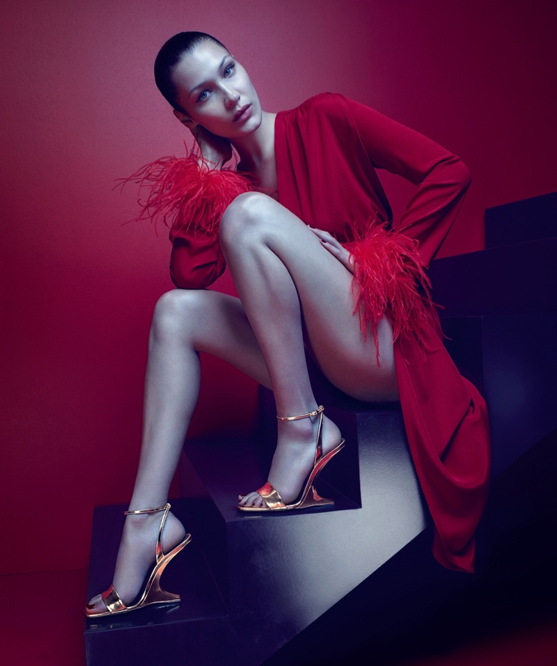 Dressed in feathers, Bella Hadid models Giuseppe Zanotti's Picard gold wedge sandal