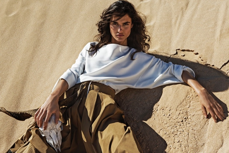 Posing in the sand, Blanca Padilla models Stradivarius long-sleeve shirt and paper bag waist skirt