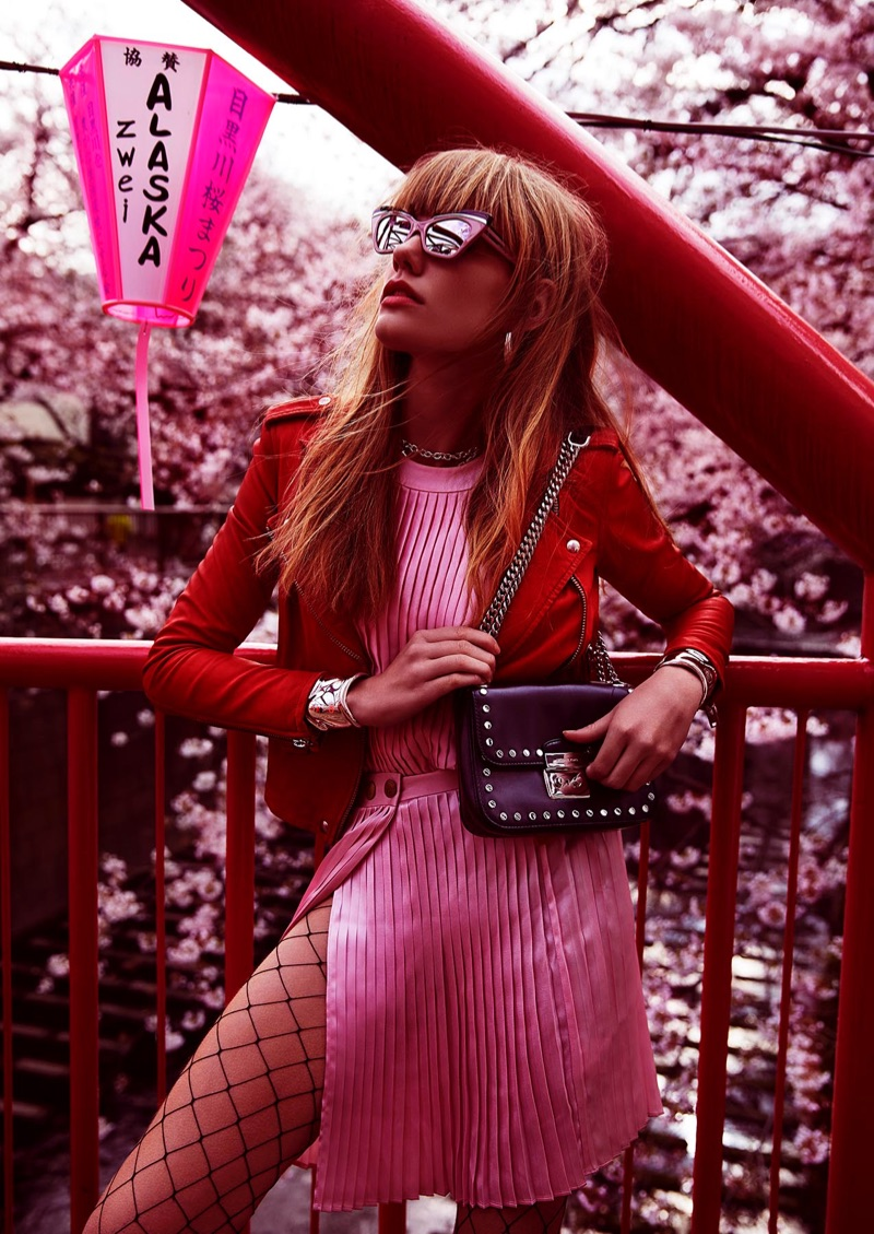 Standing out in pink, the model wears Pierre Balmain pleated top and skirt with IRO leather jacket and Michael Kors bag