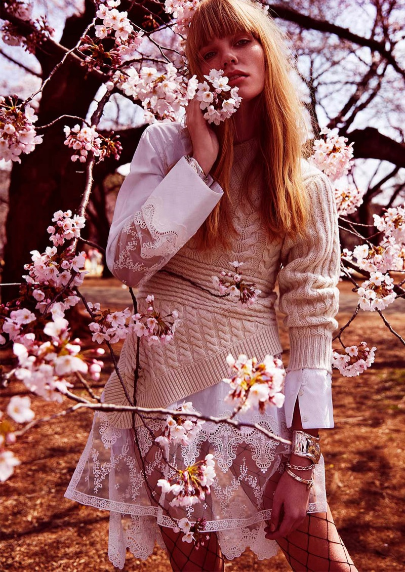 Posing next to cherry blossoms, Clara Raddatz wears Burberry one-shoulder cable knit cashmere sweater and lace cotton shirt