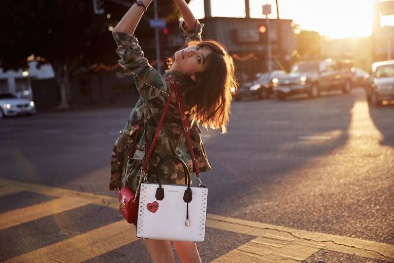 Model Hikari Mori poses in Michael Kors Scout crossbody bag with two-toned Mercer bag