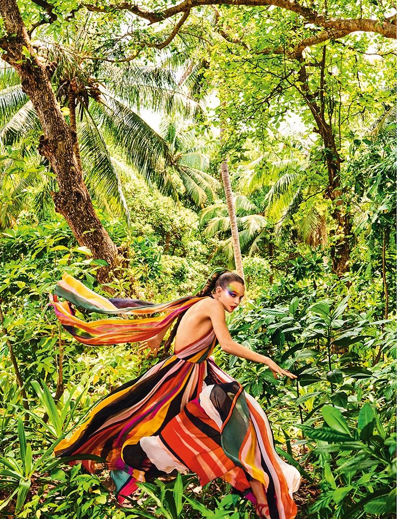 Posing in green foliage, Josephine Skriver wears Elie Saab striped dress