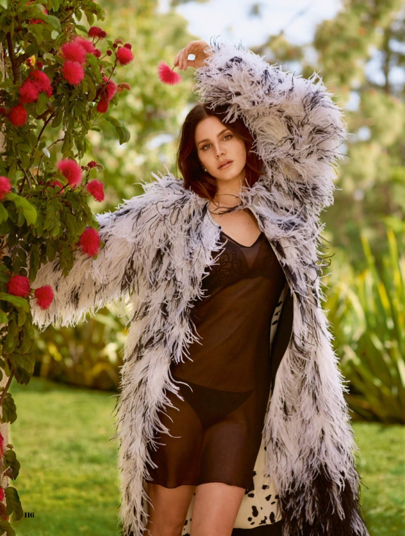 Lana Del Rey poses in Adam Lippes feather coat, Intimissimi slip dress and Dior earrings