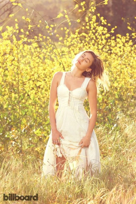 Posing outdoors, Miley Cyrus wears white maxi dress