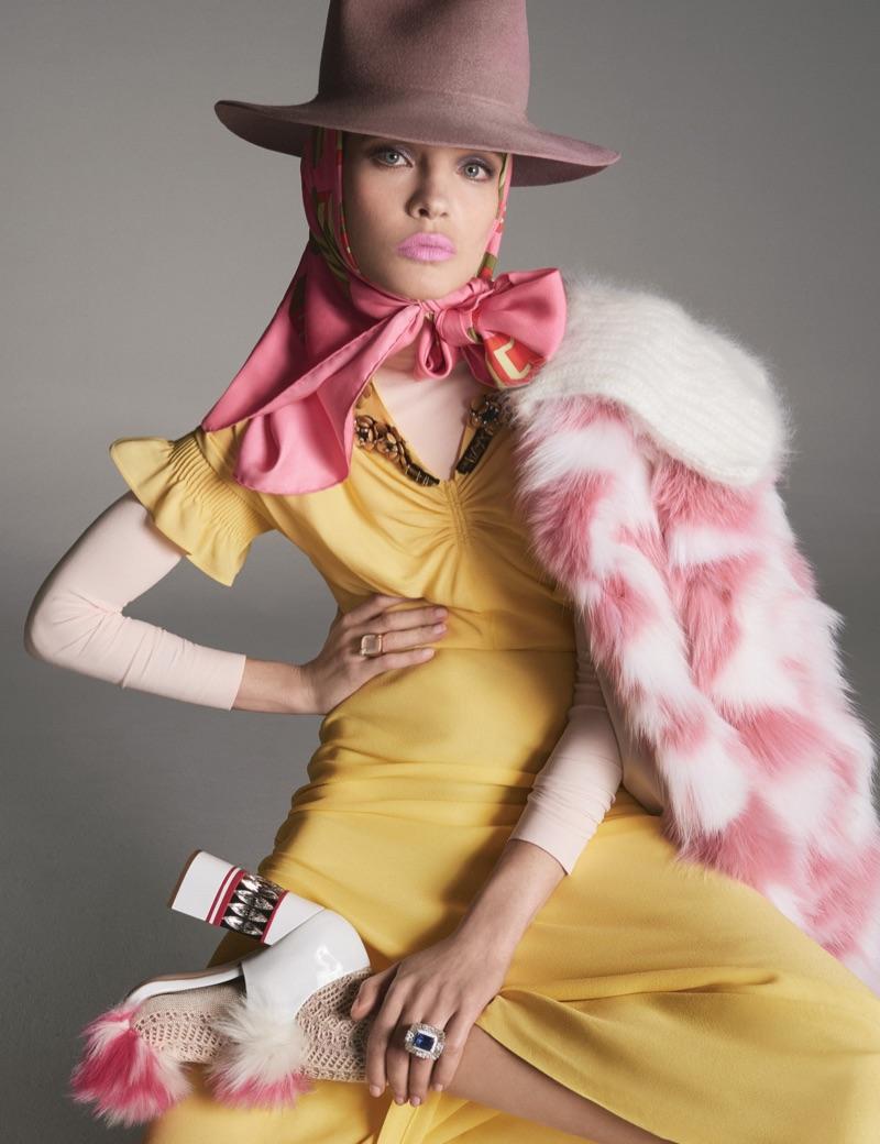 Natalia Vodianova poses in Miu Miu dress, coat and shoes with Preston & Olivia hat and Gucci scarf