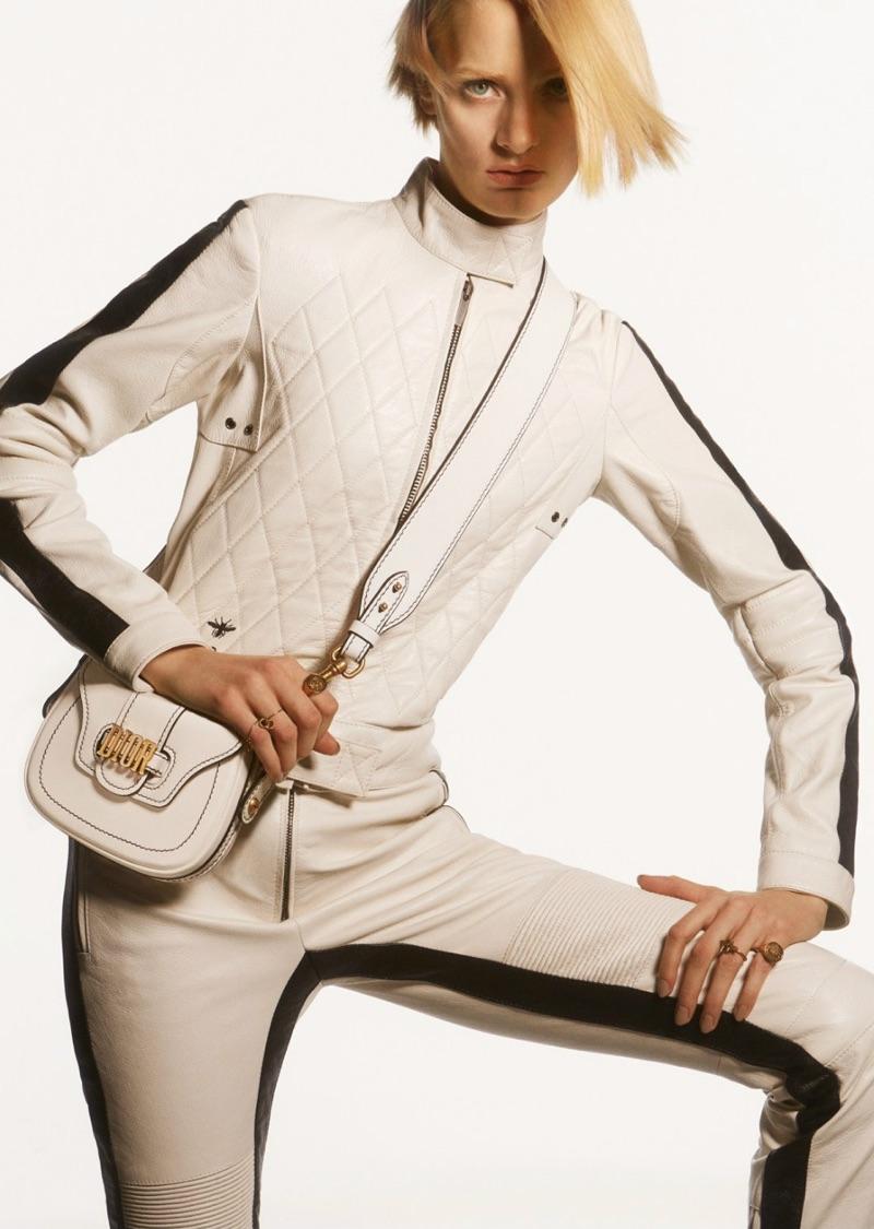 Dressed in white, Sunniva Vaatevik models Dior quilted jacket, pants and logo embellished bag
