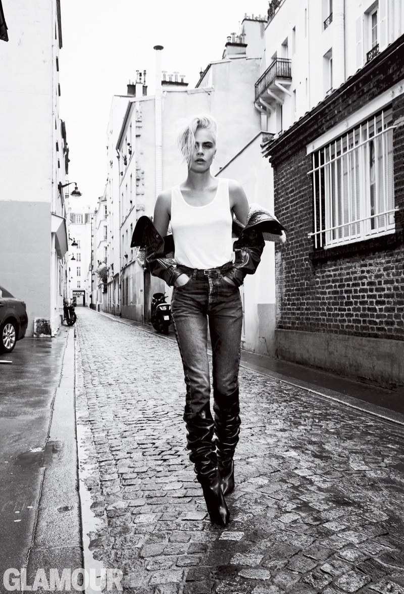 Cara Delevingne wears Saint Laurent tank, jeans, sleeves and boots