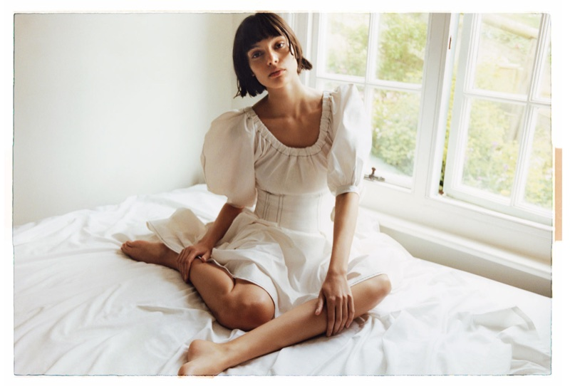 Posing in bed, Charlee Fraser wears Rejina Pyo dress