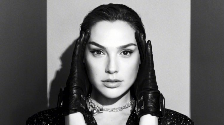 Photographed in black and white, Gal Gadot wears leather gloves and star print dress