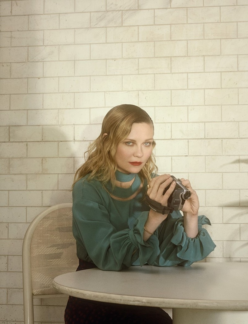 Kirsten Dunst poses with a camcorder wearing a Fendi blouse and Altuzarra skirt