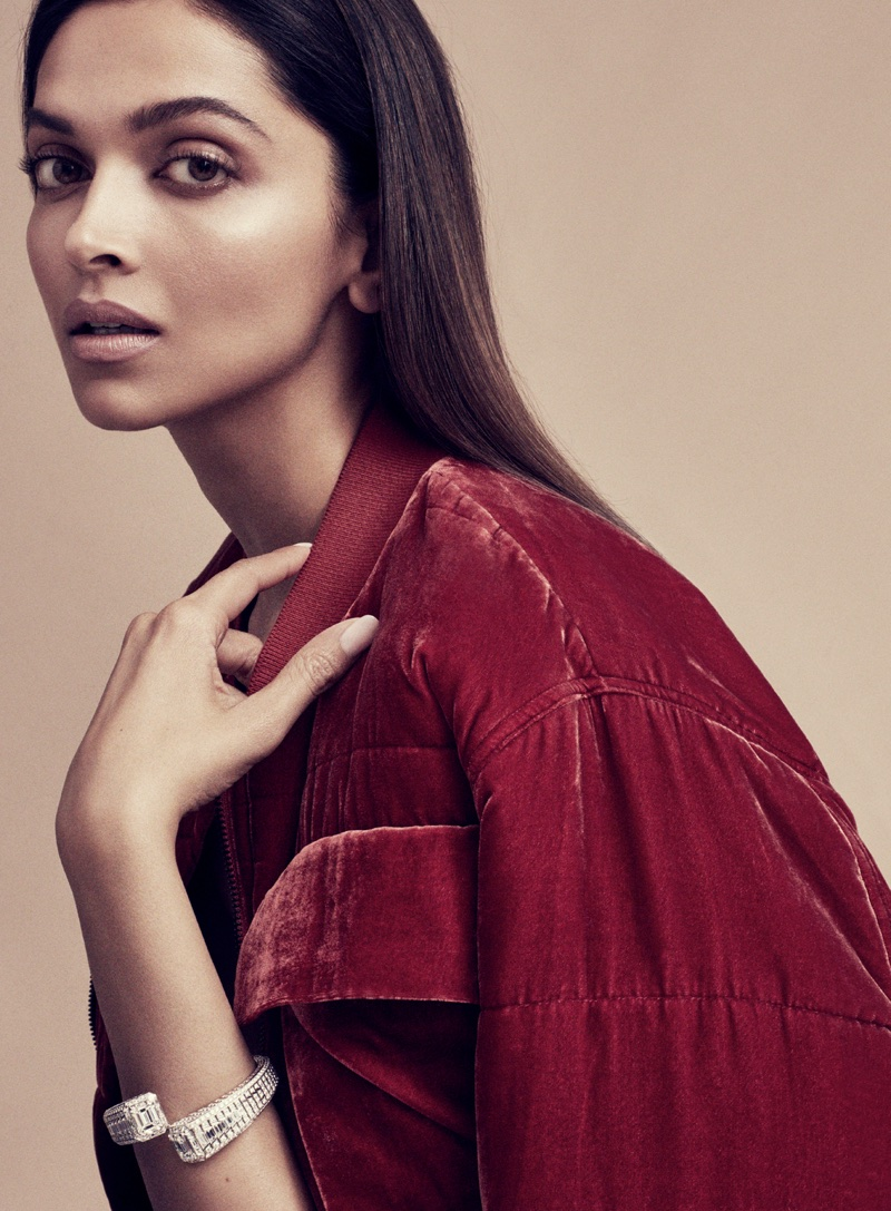 Actress Deepika Padukone covers up in a red jacket with a glittering bracelet
