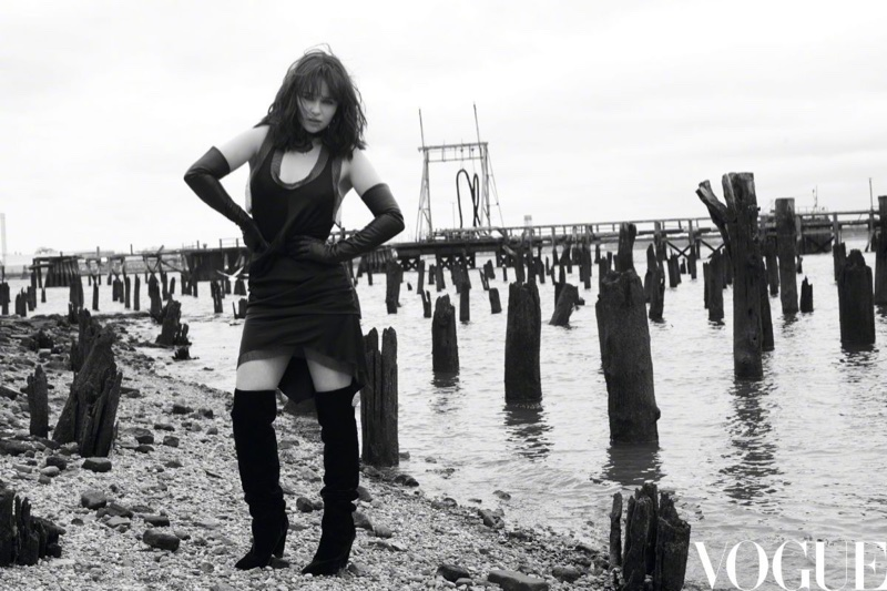 Actress Emilia Clarke strikes a pose in a black dress and knee-high boots