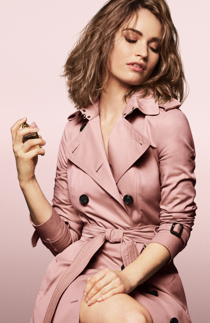 Lily James poses in a pink trench coat behind the scenes at Burberry fragrance campaign