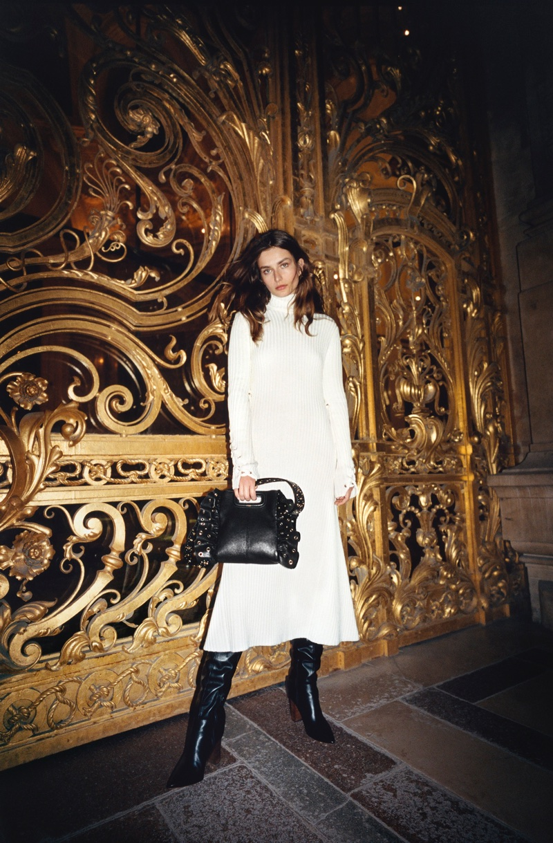 Andreea Diaconu poses in a white knit dress from Maje's fall-winter 2017 campaign